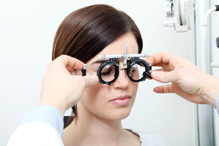 optician with trial frame, optometrist doctor examines eyesight  woman patient Stock Photo