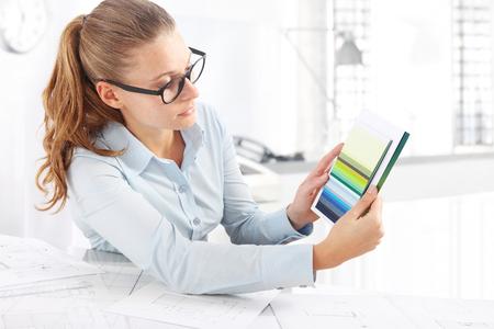 topografo: Diseñador de interiores de elegir los colores y mostrando una muestra de color en el escritorio
