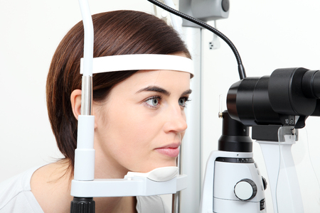 woman doing eyesight measurement with optical slit lamp 写真素材