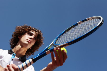 tennis player with racket during a match game isolated in blue sky