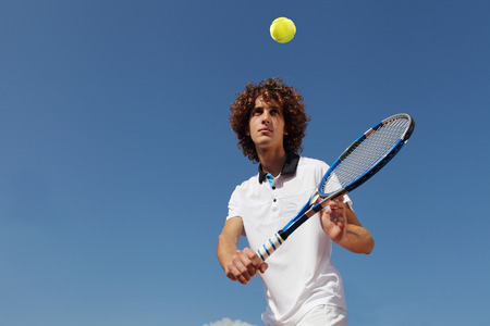 forehand: tennis player with racket during a match game isolated in blue sky