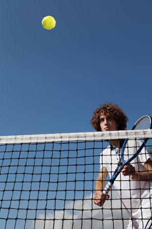 tennis player with racket during a match game in blue sky background