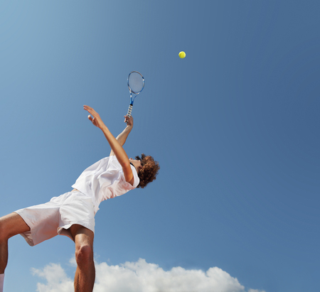 tennis player with racket during a match game  in blue sky background Reklamní fotografie