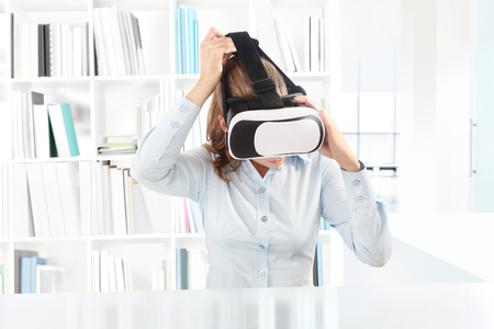 contact info: Woman wearing virtual reality goggles headset. VR glasses. 360 degrees, in office