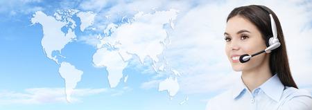 Contacteer ons, klantenservice operator vrouw met headset lachend geïsoleerd op internationale kaart blauwe achtergrond Stockfoto