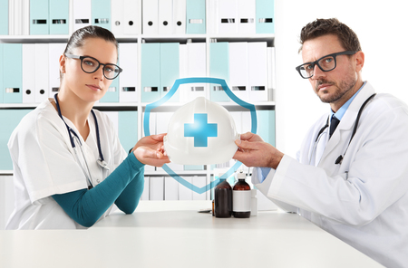 protection hands: medical health insurance concept, doctors hands with protection helmet.