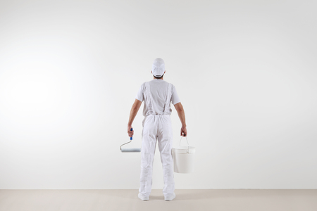 Rear view of painter man looking at blank wall, with paint roller and bucket, isolated on white room.