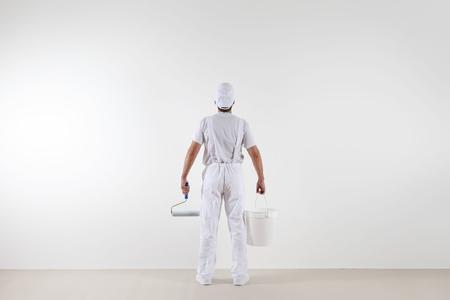 Vue arrière de l'homme peintre en regardant le mur blanc, avec rouleau à peinture et seau, isolé sur la salle blanche.