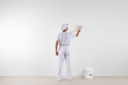 Rear view of painter man looking at blank wall, with paint brush and bucket, isolated on white room Reklamní fotografie