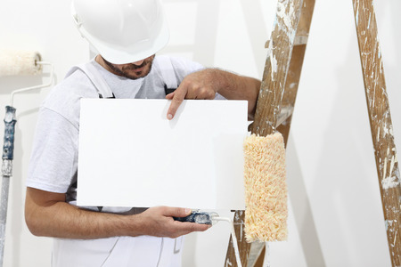 painter man showing blank white sign, with paint roller and ladder. Stock Photo