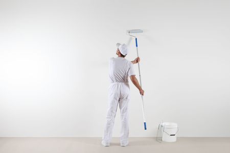 Rear view of painter man looking at blank wall, with paint stick roller and bucket, isolated on white room Reklamní fotografie - 78670923