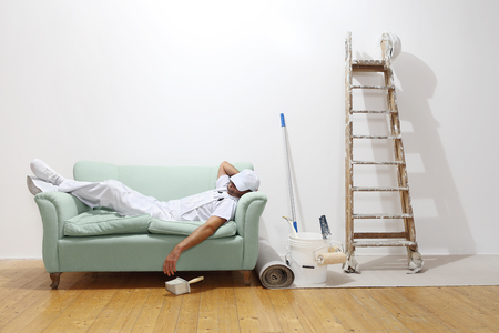 Very tired worker concept, painter man sleeps on the couch.