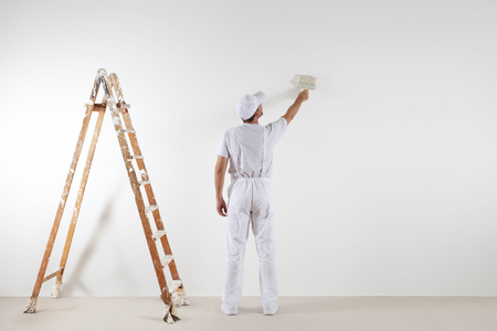 Rear view of painter man looking and painting blank wall, with paint brush and wooden ladder, isolated on white big space. Stok Fotoğraf