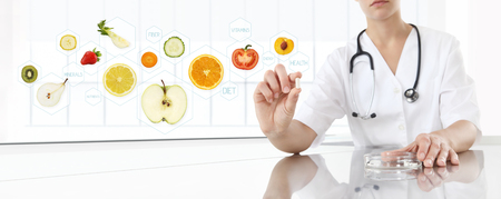 healthy food supplements concept, Hand of nutritionist doctor showing pill on symbols fruits background. Stock Photo