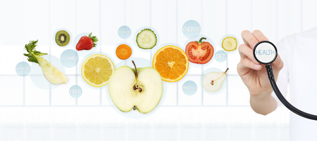 healthy food concept, Hand of nutritionist doctor pointing fruits with stethoscope. Standard-Bild