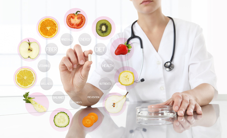 healthy food supplements concept, Hand of nutritionist doctor showing pill on symbols fruits background. Archivio Fotografico
