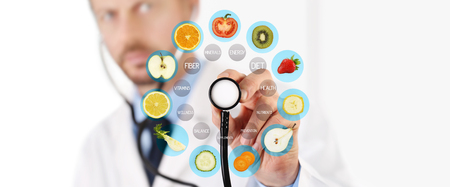 healthy food concept, Hand of nutritionist doctor pointing fruit with stethoscope.