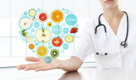 healthy food supplements concept, Hand of nutritionist doctor showing symbols fruits in heart shape.