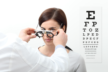 woman doing eyesight measurement with trial frame and visual test chart on white. Archivio Fotografico