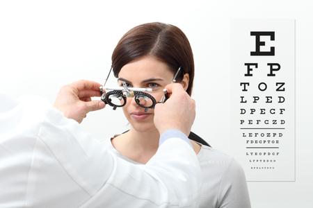 kobieta robi pomiar wzroku z ramką próbną i wizualną tabelą testową na białym tle.