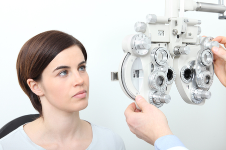 woman doing eyesight measurement with optical slit lamp.