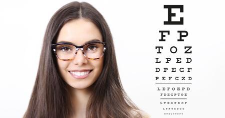 smile female face with spectacles on eyesight test chart background, eye examination ophthalmology concept.