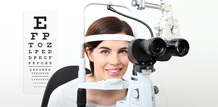 smile woman doing eyesight measurement with slit lamp and visual test chart on white. Stock Photo