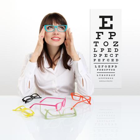 smile female face chooses spectacles on eyesight test chart background, eye examination ophthalmology concept. Standard-Bild