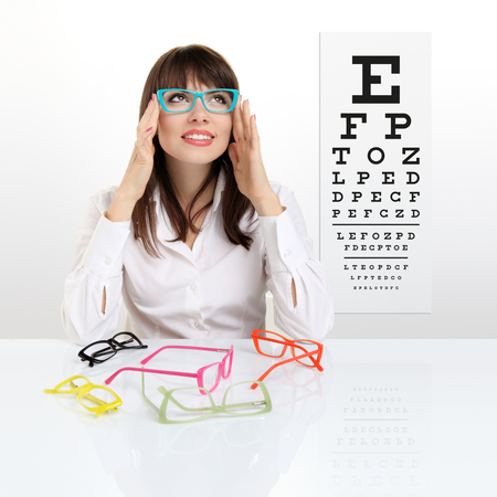 smile female face chooses spectacles on eyesight test chart background, eye examination ophthalmology concept. Archivio Fotografico