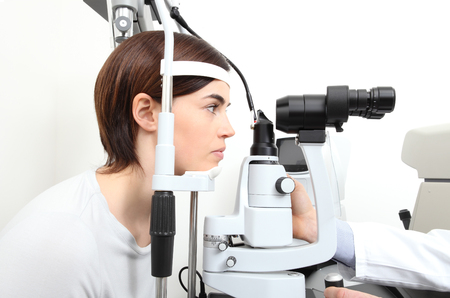 woman doing eyesight measurement with optician slit lamp.