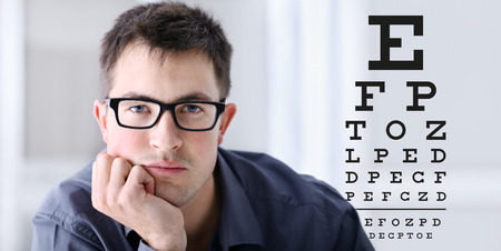 male face with spectacles on eyesight test chart background, eye examination ophthalmology concept.