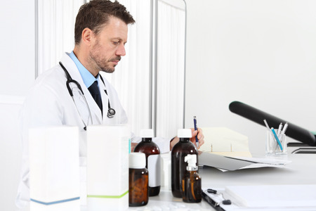 Doctor writing prescription at desk in medical office with drugs in the foreground. Stock Photo