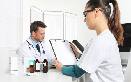 Doctors writing prescription at desk in medical office with drugs and clipboard in the foreground. Stock Photo