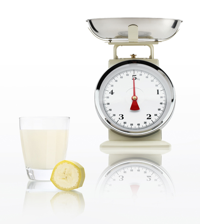alimentacion balanceada: escala de alimentos con jugo de plátano de vidrio aislado sobre fondo blanco, concepto de dieta equilibrada.