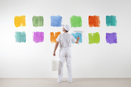 redecorate: Rear view of painter man who make and chooses from various color samples isolated on the big blank white wall.
