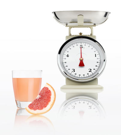 alimentacion balanceada: food scale with grapefruit juice glass isolated on white background, Balanced diet concept.