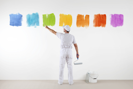 Rear view of painter man pointing with finger the colors on wall, with paint roller and bucket, isolated on white.