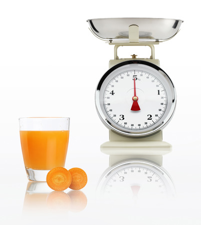 alimentacion balanceada: escala de alimentos con vidrio de jugo de zanahoria aislado sobre fondo blanco, concepto de dieta equilibrada.
