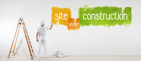 painter man with paint brush drawing under construction text isolated on the blank white wall. Stock Photo