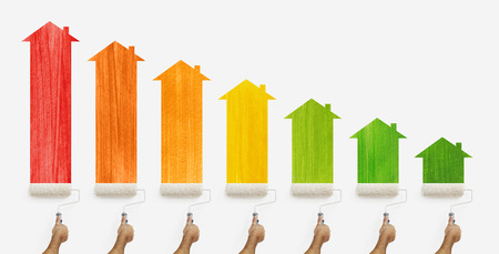 energy efficiency concept, hands with paint roller painting the colored class home and arrow chart, isolated on white background. Stock Photo
