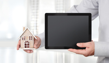 Hands with house and digital tablet, advertisement concept. Archivio Fotografico