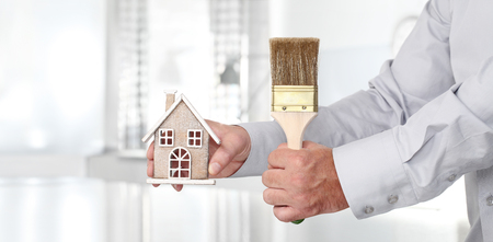 Hands with house and paint brush, home services painter concept.