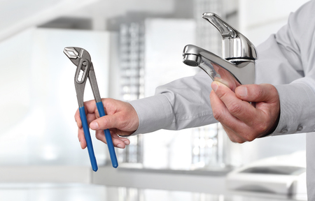 Hands with faucet and pipe wrench, install and construction home services plumber concept.