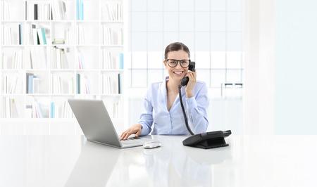 uśmiecha się kobieta w pakiecie office rozmawiać przez telefon i używać komputera siedzi na dużym pulpicie.