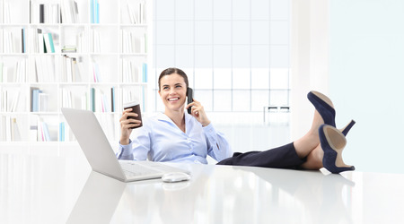 Relaxed business woman drinking coffee and talking on the phone with her feet on large desk with computer.