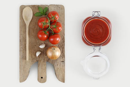 Concept of cooking with wooden cutting board, tomatos, onion,, basil, garlic and tomatoes sauce in glass jar isolated on kitchen white worktop, copy space, top view. Stock Photo