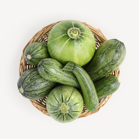 top view wicker basket of zucchini isolated on white background.