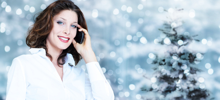 christmas theme, business smiling woman using smartphone on blurred bright lights background.