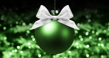 christmas ball, silver satin ribbon bow on blurred green bright lights background.