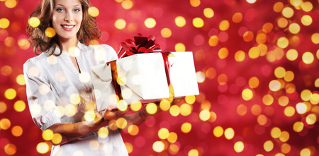 christmas shopping, woman with gift package on blurred bright lights background, banner template with copy space.